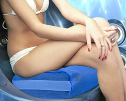 Woman louging in hot tub on blue spa cushion
