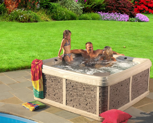 Family enjoying bubbling hot tub next to pool